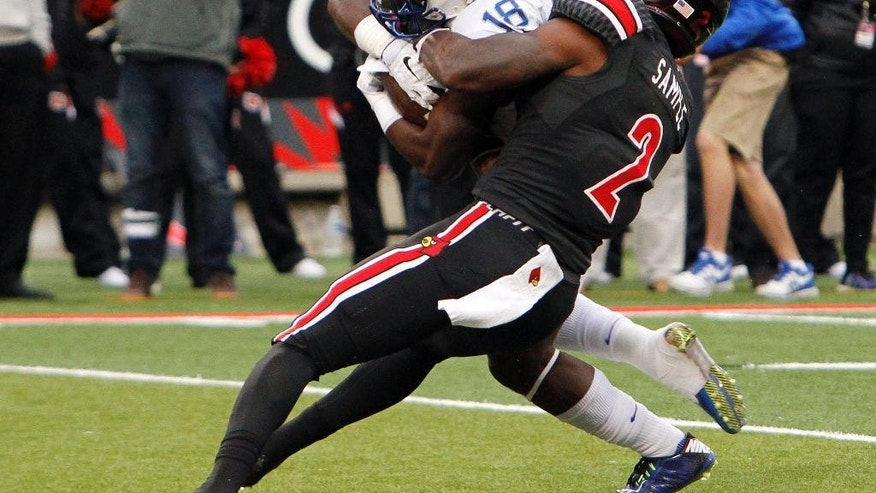 Louisville's James Sample, right, fights to tackle Kentucky's Stanley Williams during the second half of an NCAA college football game Saturday, Nov. 29, 2014, in Louisville, Ky. Louisville won 44-40. (AP Photo/Garry Jones)
