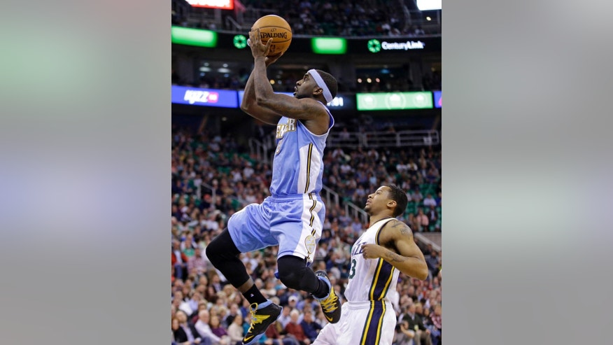 Denver Nuggets' Ty Lawson, left, shoots as Utah Jazz's Trey Burke looks on in the second quarter during an NBA basketball game Monday, Dec. 1, 2014, in Salt Lake City. (AP Photo/Rick Bowmer)