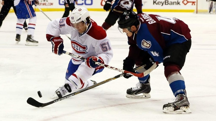 Montreal Canadiens center David Desharnais, left, battles for control of the puck with Colorado Avalanche defenseman Tyson Barrie in the first period of an NHL hockey game in Denver on Monday, Dec. 1, 2014. (AP Photo/David Zalubowski)