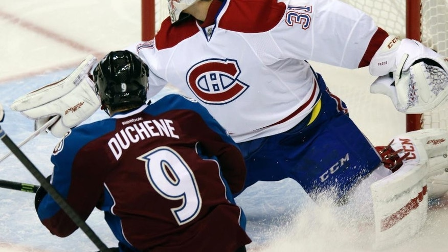Colorado Avalanche center Matt Duchene, front, looks on as his shot bangs between the pipes behind Montreal Canadiens goalie Carey Price in the second period of an NHL hockey game in Denver on Monday, Dec. 1, 2014. The puck did not go into the net on the play. (AP Photo/David Zalubowski)