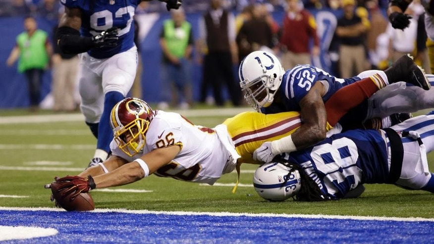 Washington Redskins tight end Jordan Reed reaches in to the end zone as he's stopped by Indianapolis Colts inside linebacker D'Qwell Jackson, top, and free safety Sergio Brown during the second half of an NFL football game Sunday, Nov. 30, 2014, in Indianapolis. Reed was called down short of the end zone.  (AP Photo/AJ Mast)