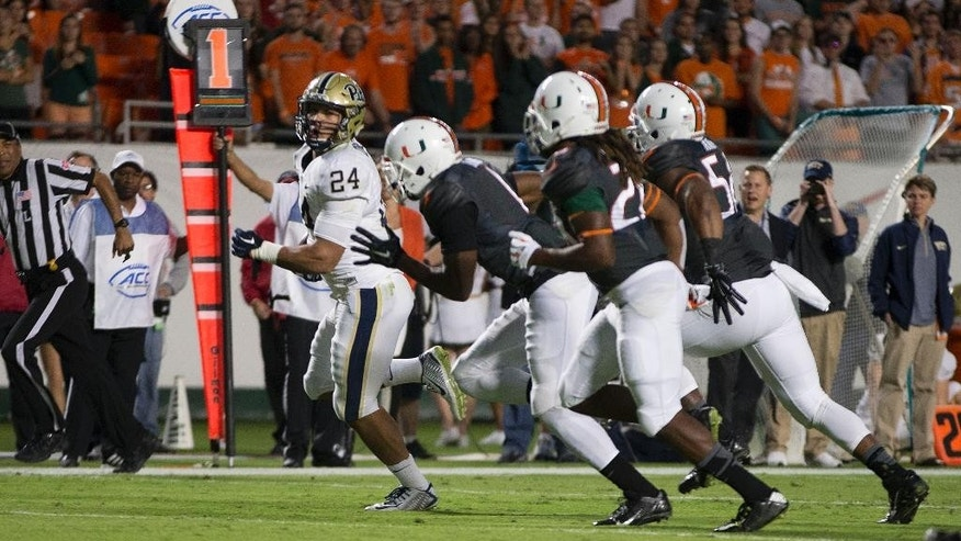 Pittsburgh's James Conner (24) runs away from the Miami players to score the first of his two touch downs during the first half of an NCAA college football game in Miami Gardens, Fla., Saturday, Nov. 29, 2014. (AP Photo/J Pat Carter)
