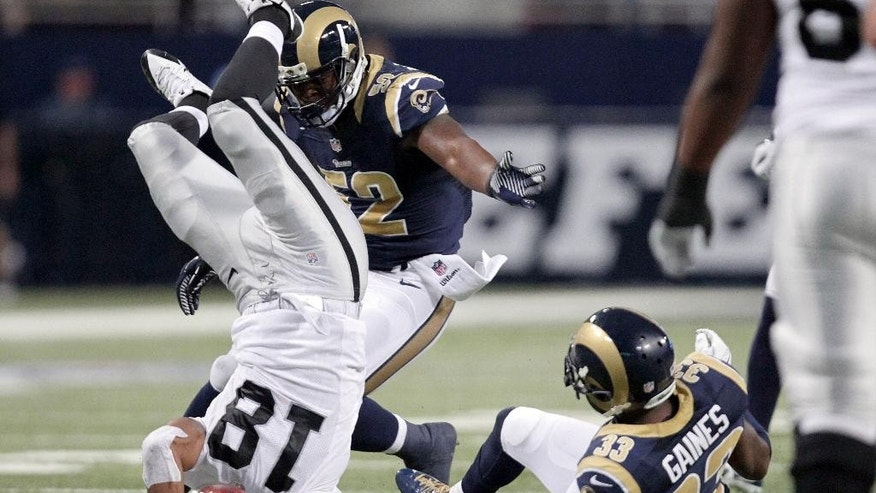 Oakland Raiders wide receiver Andre Holmes, left, is flipped into the air by St. Louis Rams cornerback E.J. Gaines, right, after catching a pass for a 6-yard gain as Rams linebacker Alec Ogletree, center, gets in on the play during the second quarter of an NFL football game Sunday, Nov. 30, 2014, in St. Louis. (AP Photo/Tom Gannam)