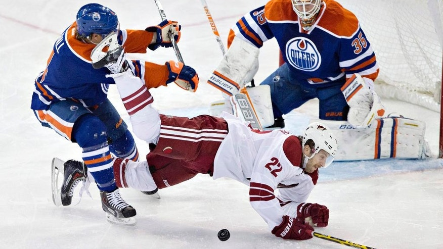 Arizona Coyotes' Brandon McMillan (22) is knocked down by Edmonton Oilers' Taylor Hall (4) as goalie Viktor Fasth (35) looks for the puck during the second period of an NHL hockey game in Edmonton, Alberta, on Monday, Dec. 1, 2014. (AP Photo/The Canadian Press, Jason Franson)