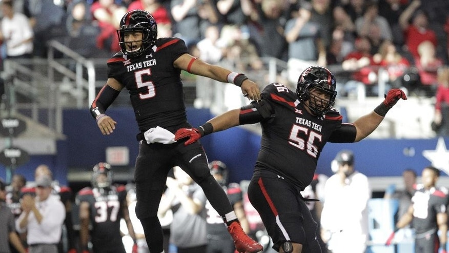Texas Tech quarterback Patrick Mahomes (5) celebrates with offensive lineman Alfredo Morales (56) after Mahomes passed for a touchdown against Baylor in the first half of an NCAA college football game, Saturday, Nov. 29, 2014, in Arlington, Texas. (AP Photo/Tim Sharp)