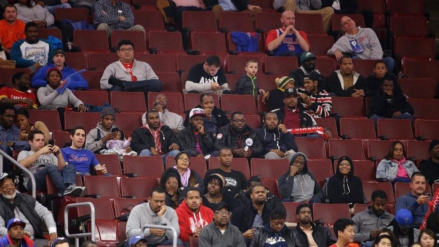 In this Dec. 1, 2014, photo, fans watch an NBA basketball game between the Philadelphia 76ers and the San Antonio Spurs in Philadelphia. The winless Philadelphia 76ers are the worst team in the NBA and on another lengthy losing streak for the second straight season. (AP Photo/Matt Slocum)