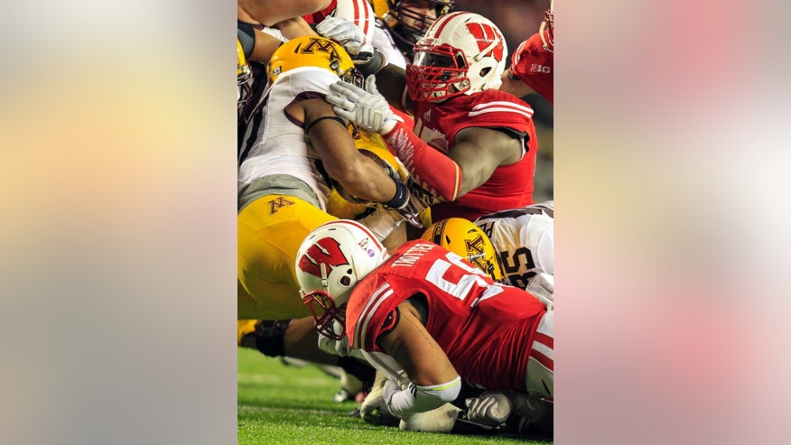 Wisconsin's Marcus Trotter (59) and Warren Herring wrap up Minnesota's David Cobb during the second half of an NCAA college football game Saturday, Nov. 29, 2014, in Madison, Wis. Wisconsin won 34-24. (AP Photo/Andy Manis)