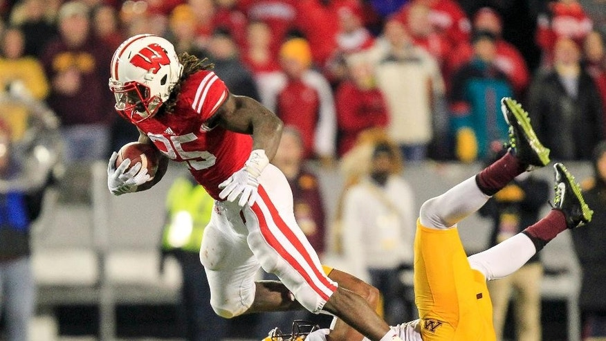 Wisconsin's Melvin Gordon (25) runs against Minnesota's Cedric Thompson during the second half of an NCAA college football game Saturday, Nov. 29, 2014, in Madison, Wis. Gordon had 151 yards in Wisconsin's 34-24 win. (AP Photo/Andy Manis)
