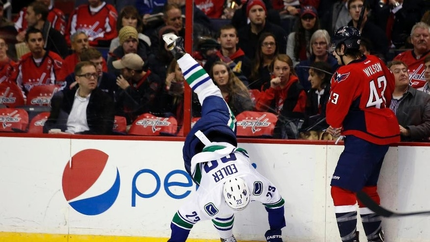 Vancouver Canucks defenseman Alexander Edler (23), from Sweden, falls after colliding with Washington Capitals right wing Tom Wilson (43) in the second period of an NHL hockey game, Tuesday, Dec. 2, 2014, in Washington. (AP Photo/Alex Brandon)