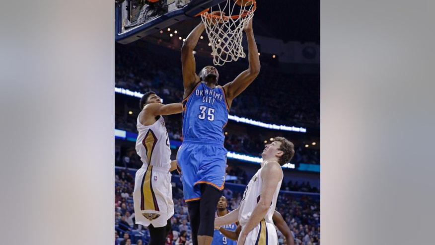 Oklahoma City Thunder forward Kevin Durant (35) is fouled by New Orleans Pelicans forward Anthony Davis, left, as he goes to the basket over center Jeff Withey, right,  in the first half of an NBA basketball game in New Orleans, Tuesday, Dec. 2, 2014. (AP Photo/Gerald Herbert)