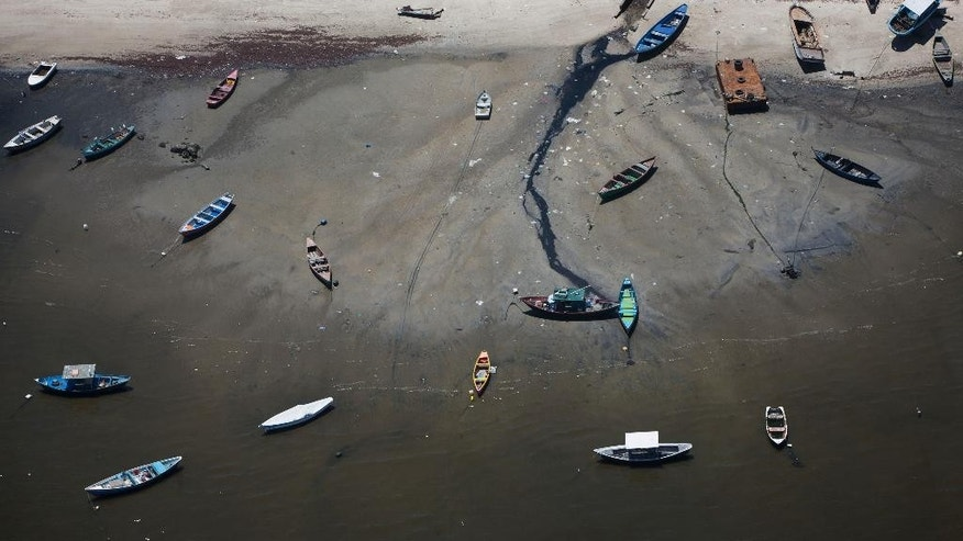 FILE - This Nov. 19, 2013 file photo shows small boats on the shore of Guanabara Bay in the suburb of Sao Goncalo, across the bay from Rio de Janeiro, Brazil. Brazil's Tourism Ministry has removed from its Instagram feed a photomontage that pictures the bay where Olympic sailing events will take place as a tropical paradise of crystalline waters - a far cry from the reality of its brackish, sewage-filled waters. The photomontage was posted late Sunday, Nov. 30, 2014. Nearly 70 percent of the sewage in greater Rio goes untreated, flowing raw into area rivers, onto the beaches and into the Guanabara Bay. (AP Photo/Felipe Dana, File)