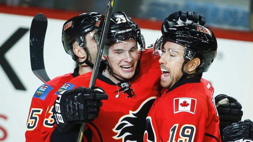 Calgary Flames' David Jones, right, celebrates his goal with teammate Sean Monahan during first period NHL hockey action against the Arizona Coyotes in Calgary, Alberta, Tuesday, Dec. 2, 2014.    (AP Photo/The Canadian Press, Jeff McIntosh)