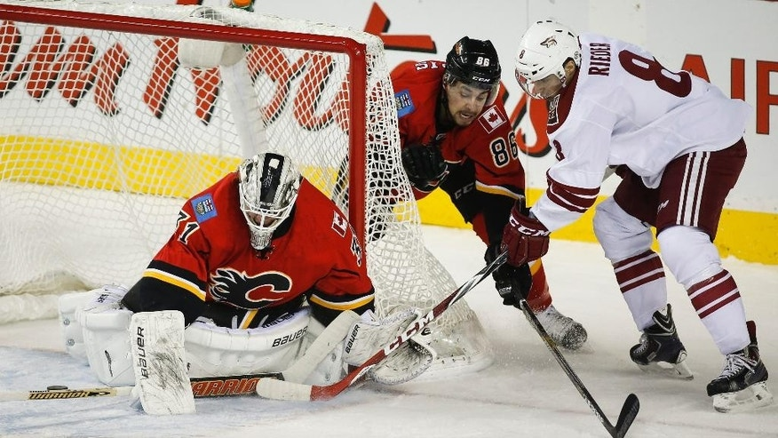 Arizona Coyotes' Tobias Rieder, right, from Germany, tries to get the puck past Calgary Flames goalie Karri Ramo, left, from Finland, as Josh Jooris looks on during first period NHL hockey action in Calgary, Alberta, Tuesday, Dec. 2, 2014.    (AP Photo/The Canadian Press, Jeff McIntosh)
