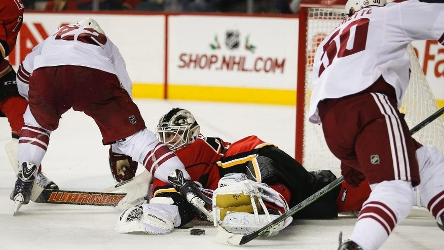Arizona Coyotes' Brandon McMillan, left, and Antoine Vermette, right, dig for a rebound from Calgary Flames goalie Karri Ramo, from Finland, during second period NHL hockey action in Calgary, Alberta, Tuesday, Dec. 2, 2014.  (AP Photo/The Canadian Press, Jeff McIntosh)