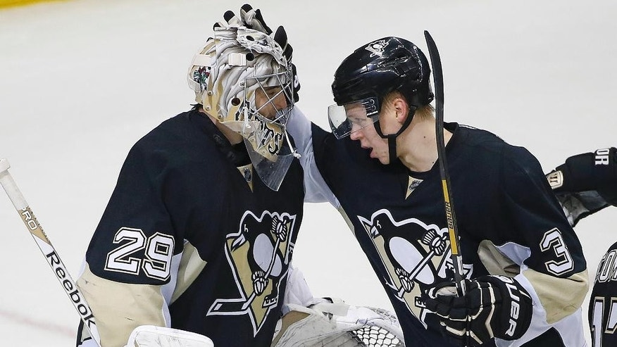 Pittsburgh Penguins goalie Marc-Andre Fleury (29) celebrates with defenseman Olli Maatta (3) after a 1-0 shutout win over the New Jersey Devils in an NHL hockey game in Pittsburgh, Tuesday, Dec. 2, 2014. (AP Photo/Gene J. Puskar