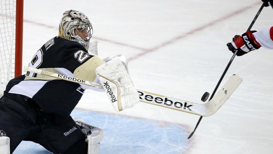 Pittsburgh Penguins goalie Marc-Andre Fleury (29) swats at a rebound during the first period of an NHL hockey game against the New Jersey Devils, in Pittsburgh, Tuesday, Dec. 2, 2014. (AP Photo/Gene Puskar)