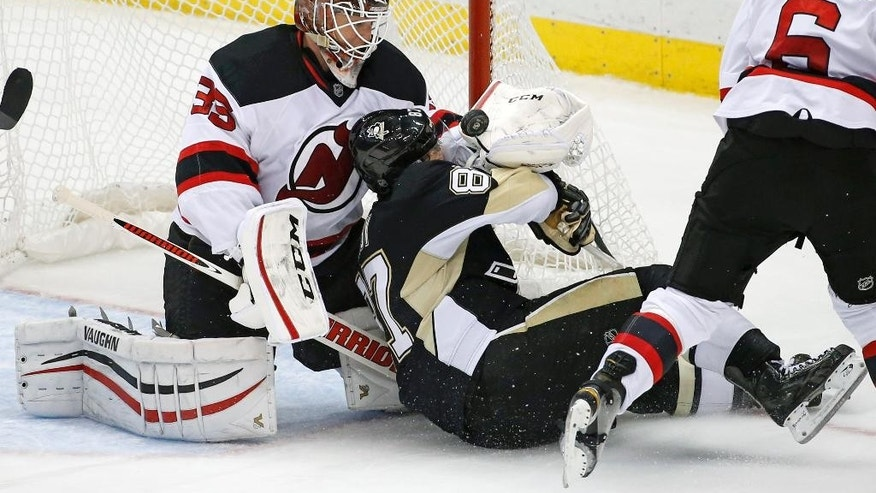 Pittsburgh Penguins' Sidney Crosby (87) slides into the glove of New Jersey Devils goalie Cory Schneider, knocking the puck out, after Schneider made a glove save on a shot by Crosby during the third period of an NHL hockey game in Pittsburgh Tuesday, Dec. 2, 2014. The Penguins won 1-0. (AP Photo/Gene J. Puskar