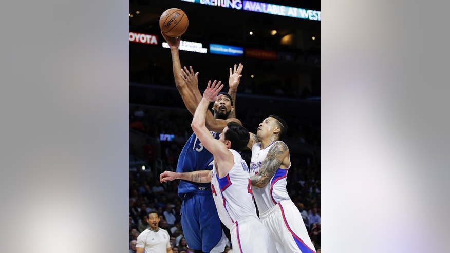 Minnesota Timberwolves' Corey Brewer, top, shoots as he is defended by Los Angeles Clippers' J.J. Redick, center, and Matt Barnes during the first half of an NBA basketball game Monday, Dec. 1, 2014, in Los Angeles. (AP Photo/Jae C. Hong)