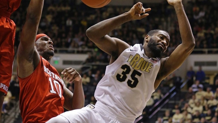 Purdue guard Rapheal Davis, right, is fouled by North Carolina State forward Lennard Freeman in the first half of an NCAA college basketball game in West Lafayette, Ind., Tuesday, Dec. 2, 2014.  (AP Photo/Michael Conroy)