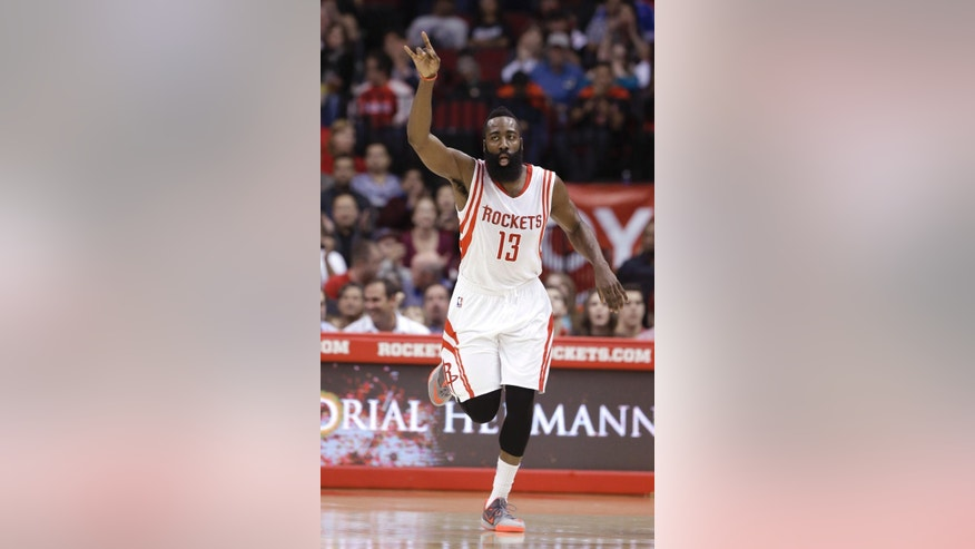 Houston Rockets' James Harden raises his hand after scoring two points against the Sacramento Kings in the first half of an NBA basketball game Wednesday, Nov. 26, 2014, in Houston. (AP Photo/Pat Sullivan)