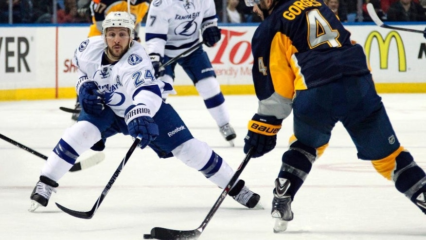 Buffalo Sabres' Josh Gorges (4) controls the puck against Tampa Bay Lightning's Ryan Callahan (24) during the first period of an NHL hockey game Tuesday, Dec. 2, 2014, in Buffalo, N.Y. (AP Photo/Jen Fuller)