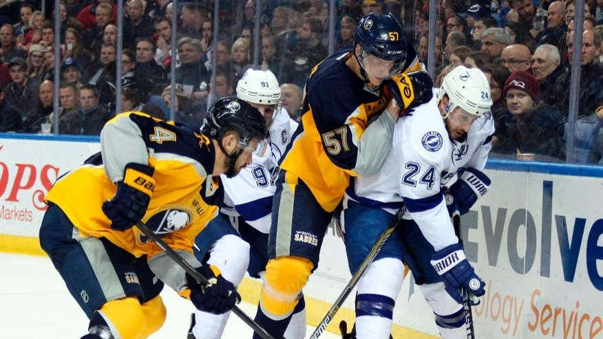 Buffalo Sabres' Tyler Myers (57) and Josh Gorges (4) battle for the puck along the boards against Tampa Bay Lightning's Ryan Callahan (24) and Steven Stamkos (91) during the first period of an NHL hockey game Tuesday, Dec. 2, 2014, in Buffalo, N.Y. (AP Photo/Jen Fuller)