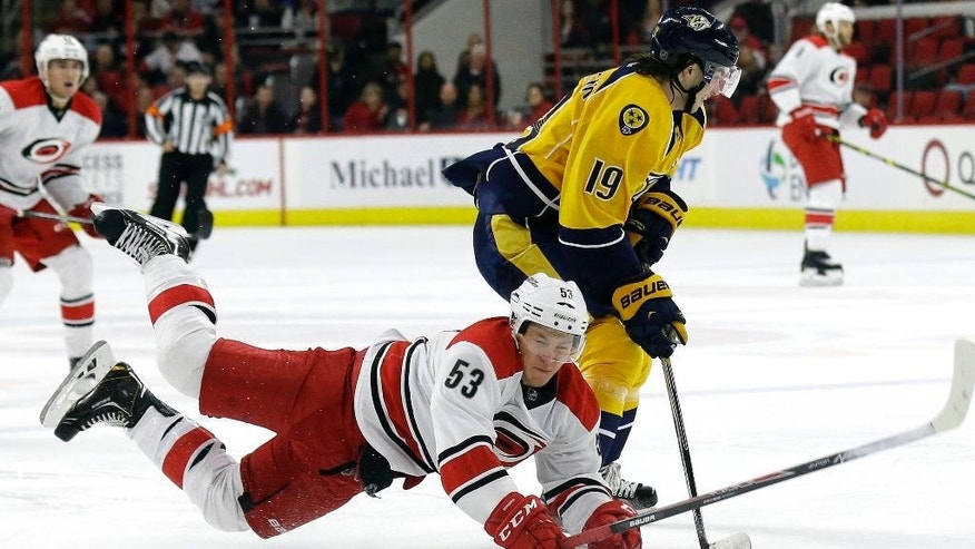 Carolina Hurricanes' Jeff Skinner (53) falls while chasing the puck with Nashville Predators' Calle Jarnkrok (19), of Sweden, during the second period of an NHL hockey game in Raleigh, N.C., Tuesday, Dec. 2, 2014. (AP Photo/Gerry Broome)