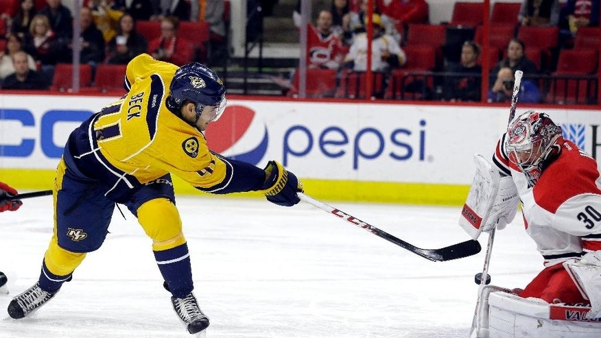 Carolina Hurricanes goalie Cam Ward (30) blocks Nashville Predators' Taylor Beck during the first period of an NHL hockey game in Raleigh, N.C., Tuesday, Dec. 2, 2014. (AP Photo/Gerry Broome)