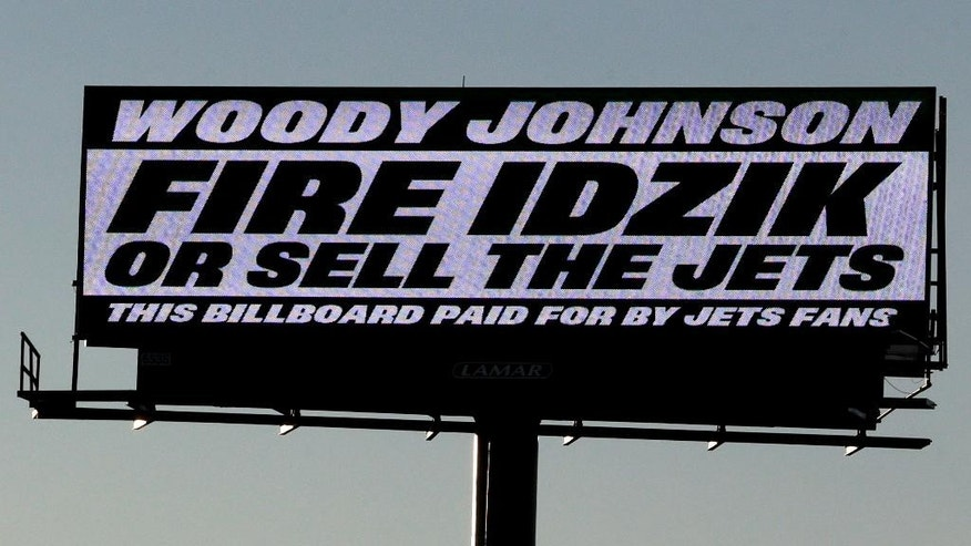 A sign directed at New York Jets owner Woody Johnson is seen on the side of Route 3 near MetLife Stadium, Friday, Nov. 28, 2014, in East Rutheford, N.J. The sign, apparently paid by Jets fans, calls for the firing of general manager John Idzik.  (AP Photo/Julio Cortez)