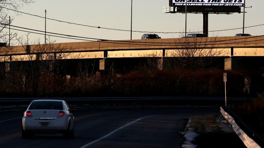 A sign directed at New York Jets owner Woody Johnson is seen on the side of Route 3 near the MetLif Stadium, Friday, Nov. 28, 2014, in East Rutheford, N.J. The sign, apparently paid by Jets fans, calls for the firing of general manager John Idzik.  (AP Photo/Julio Cortez)