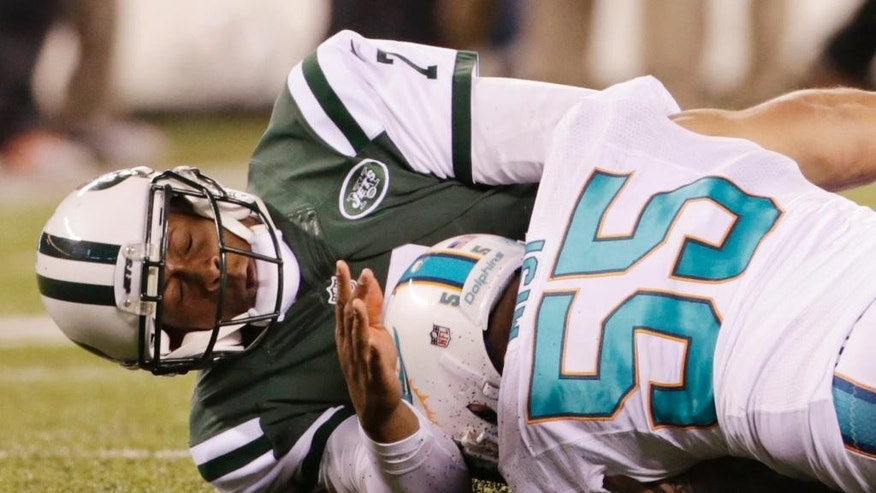 New York Jets quarterback Geno Smith (7) hits the ground as he is hit by Miami Dolphins outside linebacker Koa Misi (55) while throwing in the fourth quarter of an NFL football game, Monday, Dec. 1, 2014, in East Rutherford, N.J. The Dolphins won 16-13.  (AP Photo/Julio Cortez)