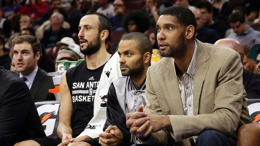 San Antonio Spurs' Tim Duncan, from right, Tony Parker, of France, and Manu Ginobili, of Argentina, watch from the bench during the first half of an NBA basketball game against the Philadelphia 76ers, Monday, Dec. 1, 2014, in Philadelphia. (AP Photo/Matt Slocum)
