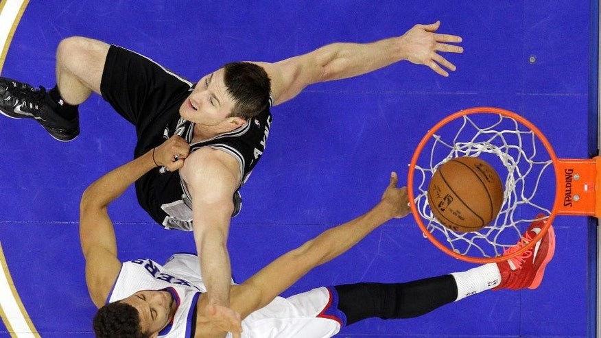Philadelphia 76ers' Michael Carter-Williams, bottom, dunks the ball past San Antonio Spurs' Aron Baynes, of Australia, during the first half of an NBA basketball game, Monday, Dec. 1, 2014, in Philadelphia. (AP Photo/Matt Slocum)