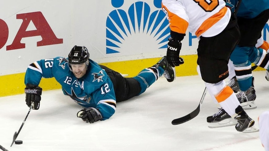 San Jose Sharks center Patrick Marleau (12) lunges for the puck next to Philadelphia Flyers defenseman Nicklas Grossmann (8), of Sweden, during the second period of an NHL hockey game Tuesday, Dec. 2, 2014, in San Jose, Calif. (AP Photo/Marcio Jose Sanchez)