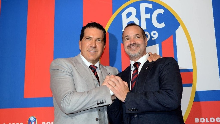 "FILE - In this Thursday, Oct. 16, 2014 file photo Joe Tacopina, right, and Joey Saputo pose in front of the Bologna Football Club logo, in Bologna, Italy. New Bologna owners Joe Tacopina and Joey Saputo have issued a joint statement on the club's website reassuring fans that they are still collaborating amid reports of a rift. They say, ""From the start we have been partners and friends and that hasn't changed. ... We will try to assure adequate financial resources for the club for many years."" New York lawyer Tacopina and Montreal Impact president Saputo purchased Bologna in October. (AP Photo/Gianfilippo Oggioni, File)"