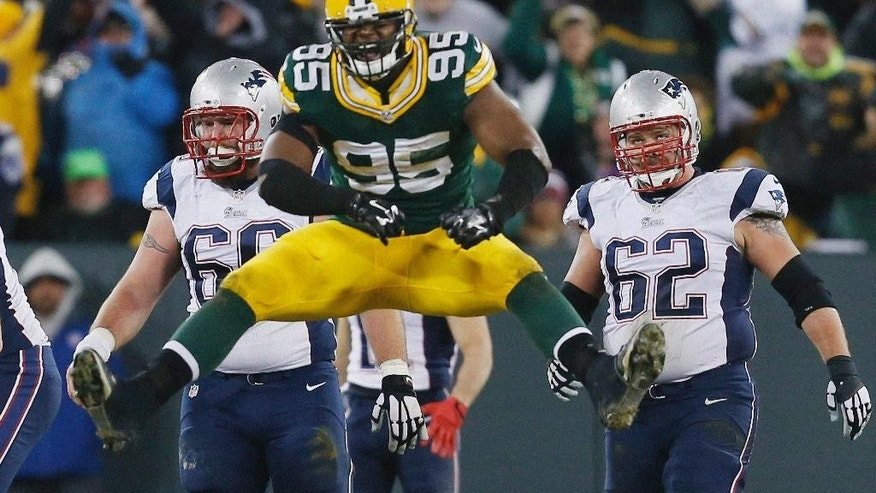 New England Patriots' Bryan Stork (66) and Ryan Wendell Wduring watch as Green Bay Packers' Datone Jones celebrates after Tom Brady was sacked the second half of an NFL football game Sunday, Nov. 30, 2014, in Green Bay, Wis. (AP Photo/Mike Roemer)