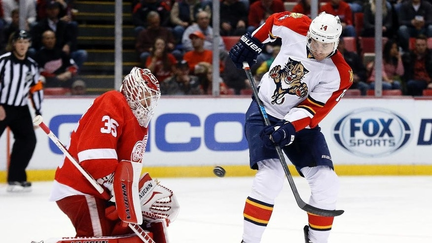 Florida Panthers left wing Tomas Fleischmann (14) tries to deflect a shot past Detroit Red Wings goalie Jimmy Howard (35) in the first period during an NHL hockey game in Detroit Tuesday, Dec. 2, 2014. (AP Photo/Paul Sancya)