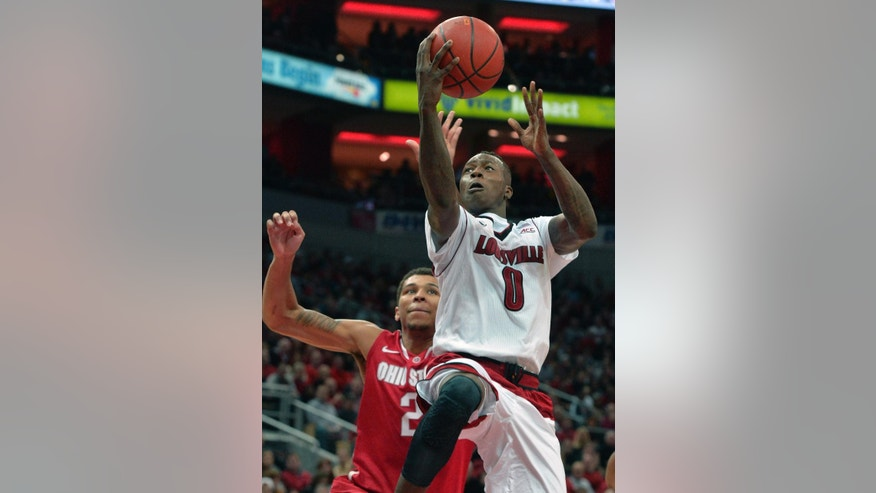 Louisville's Terry Rozier, front, goes in for a layup past the defense of Ohio State's Marc Loving during the first half of an NCAA college basketball game Tuesday, Dec. 2, 2014, in Louisville, Ky. (AP Photo/Timothy D. Easley)