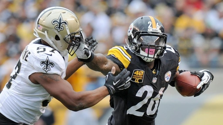 Pittsburgh Steelers running back Le'Veon Bell (26) runs the ball as New Orleans Saints inside linebacker David Hawthorne (57) pursues in the first quarter of the NFL game , Sunday, Nov. 30, 2014 in Pittsburgh. (AP Photo/Don Wright)