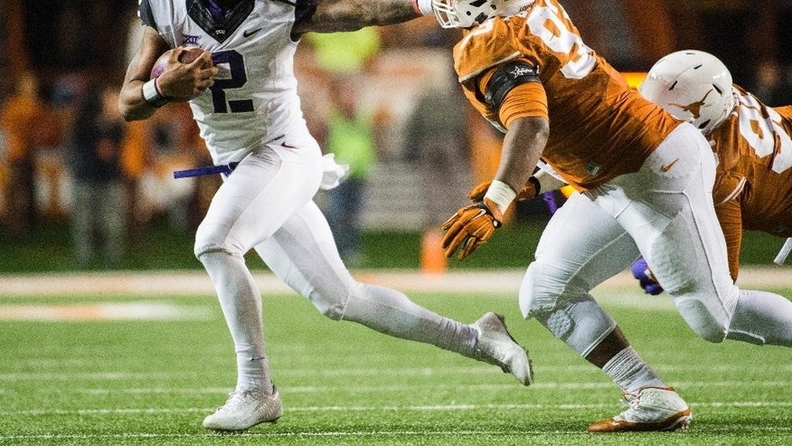 CORRECTS NAME OF TCU PLAYER TO TREVONE BOYKIN -  TCU's Trevone Boykin (2) holds off Texas' Paul Boyette Jr. (93) during the second half of an NCAA college football game, Thursday, Nov. 27, 2014, in Austin, Texas. (AP Photo/Ashley Landis)