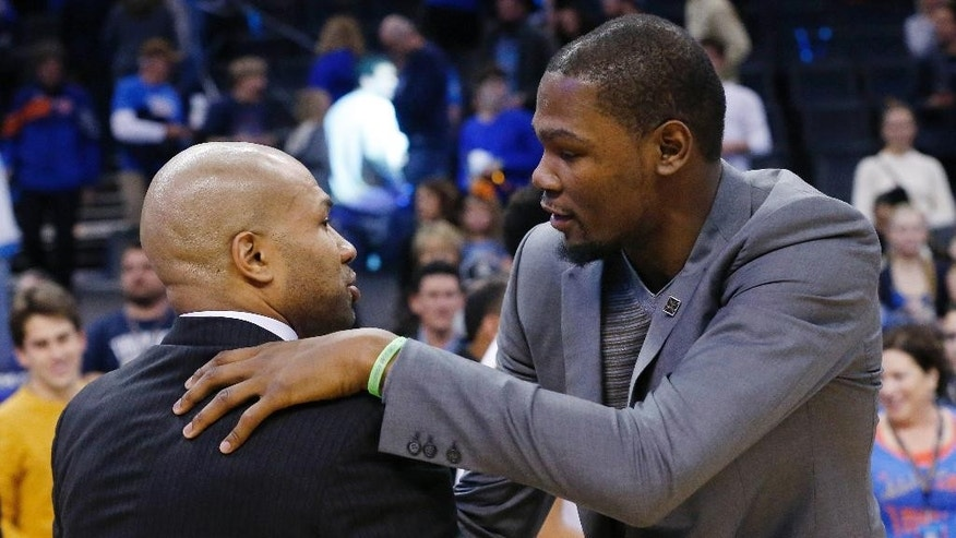 Injured Oklahoma City Thunder's Kevin Durant, right, embraces New York Knicks head coach Derek Fisher, left, following their NBA basketball game in Oklahoma City, Friday, Nov. 28, 2014. Oklahoma City won 105-78. (AP Photo/Sue Ogrocki)