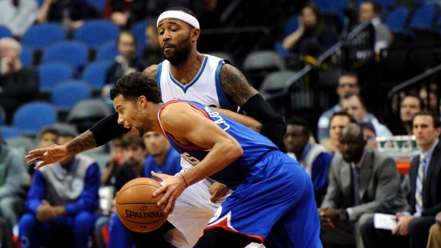 Philadelphia 76ers guard Michael Carter-Williams, in blue, drives against Minnesota Timberwolves guard Mo Williams during the first quarter of an NBA basketball game Wednesday, Dec. 3, 2014, in Minneapolis. (AP Photo/Hannah Foslien)
