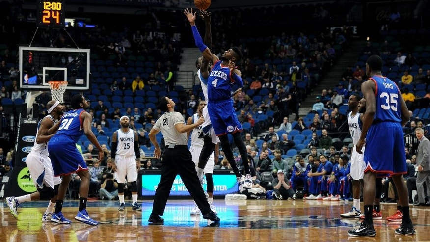 Minnesota Timberwolves center Gorgui Dieng, of Senegal, tips off against Philadelphia 76ers forward Nerlens Noel, center right, for the second time to start an NBA basketball game Wednesday, Dec. 3, 2014, in Minneapolis. The tip-off was redone after the players were facing the wrong baskets the first time. (AP Photo/Hannah Foslien)