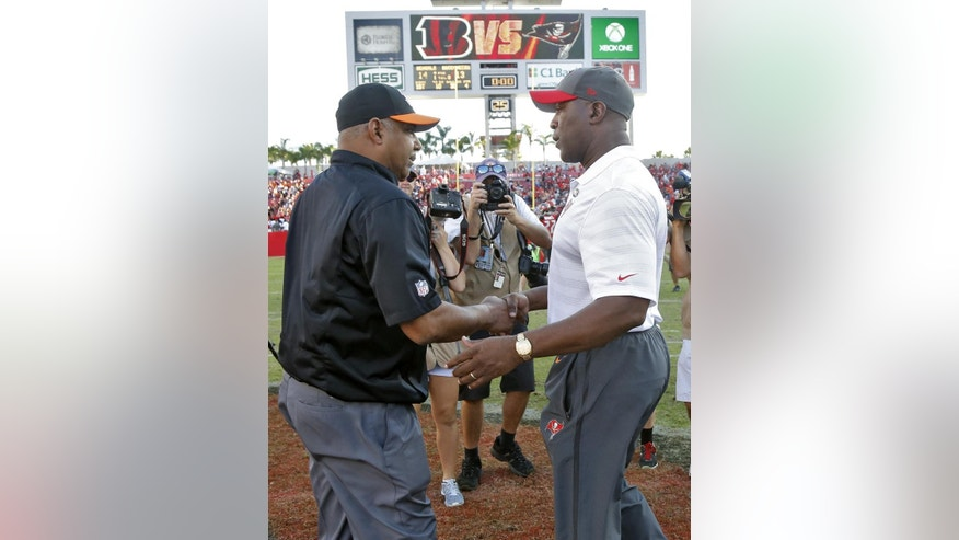 Cincinnati Bengals head coach Marvin Lewis, left, shakes hands with Tampa Bay Buccaneers head coach Lovie Smith after the Bengals defeated the Buccaneers 14-13 during an NFL football game Sunday, Nov. 30, 2014, in Tampa, Fla. (AP Photo/Brian Blanco)