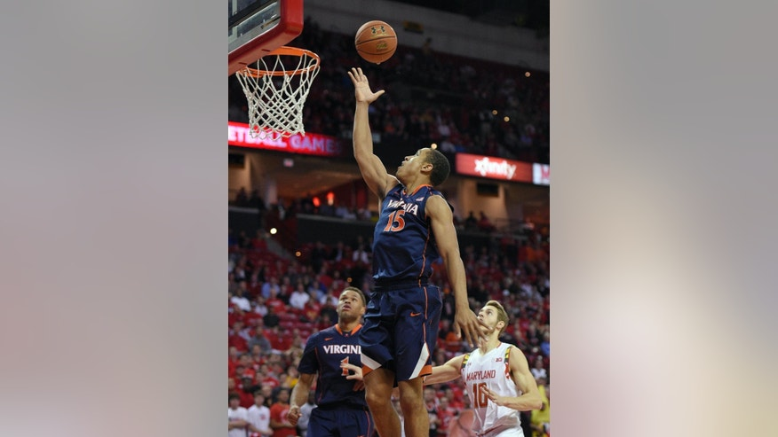 Virginia guard Malcolm Brogdon (15) goes to the basket against Maryland guard/forward Jake Layman (10) during the first half of an NCAA college basketball game, Wednesday, Dec. 3, 2014, in College Park, Md. Also seen is Virginia guard Justin Anderson (1). (AP Photo/Nick Wass)