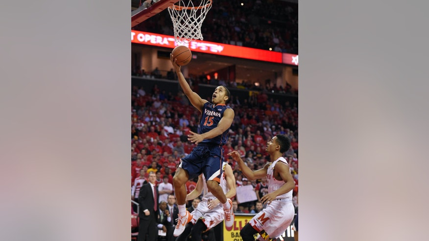 Virginia guard Malcolm Brogdon (15) goes to the basket against Maryland guard Melo Trimble, right, during the first half of an NCAA college basketball game, Wednesday, Dec. 3, 2014, in College Park, Md. (AP Photo/Nick Wass)