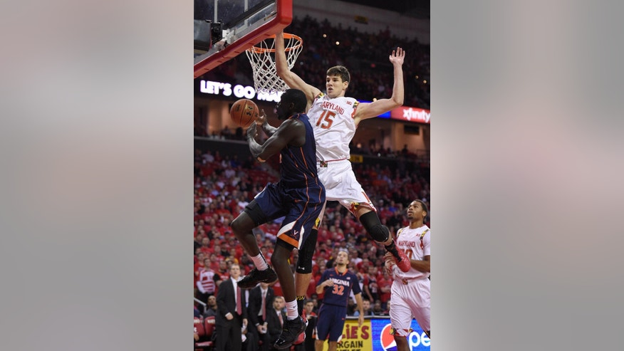 Virginia guard Marial Shayok, left, goes to the basket against Maryland forward Michal Cekovsky (15) during the first half of an NCAA college basketball game, Wednesday, Dec. 3, 2014, in College Park, Md. (AP Photo/Nick Wass)
