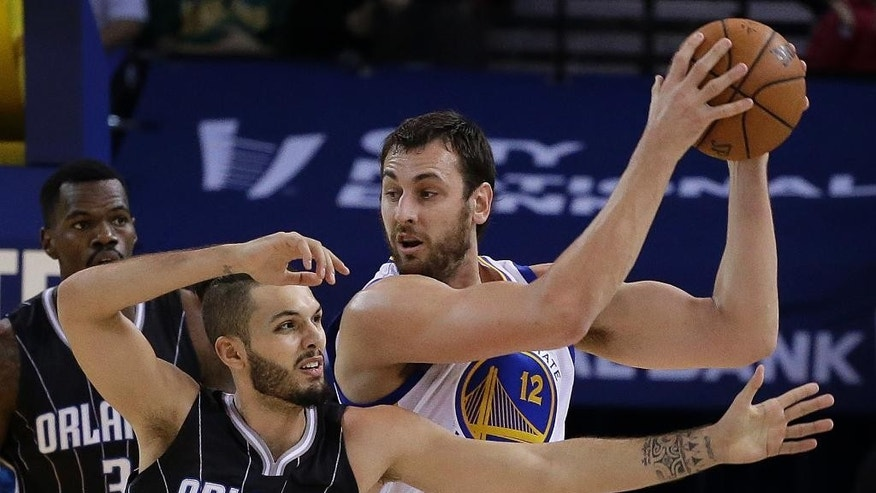 Golden State Warriors' Andrew Bogut, right, keeps the ball from Orlando Magic guard Evan Fournier (10) during the first half of an NBA basketball game Tuesday, Dec. 2, 2014, in Oakland, Calif. (AP Photo/Ben Margot)