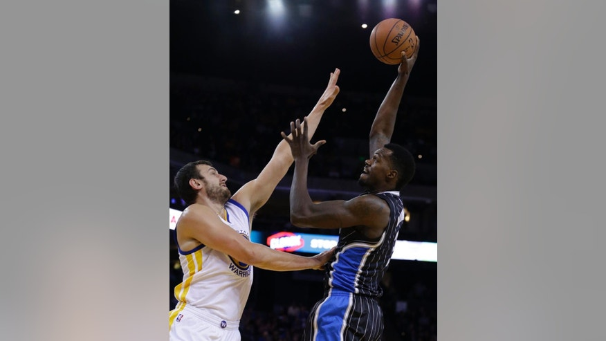 Orlando Magic center Dewayne Dedmon, right, shoots against Golden State Warriors' Andrew Bogut during the first half of an NBA basketball game Tuesday, Dec. 2, 2014, in Oakland, Calif. (AP Photo/Ben Margot)