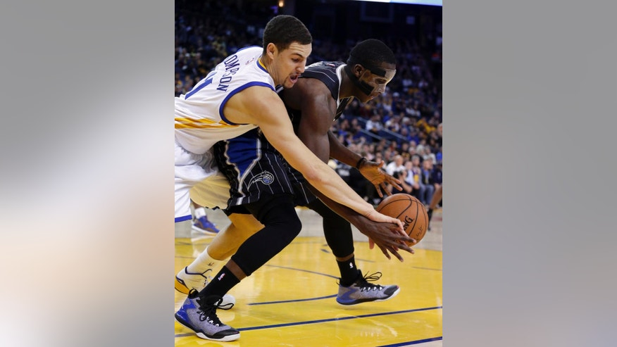Orlando Magic guard Victor Oladipo, right, and Golden State Warriors' Klay Thompson (11) fight for a loose ball during the first half of an NBA basketball game Tuesday, Dec. 2, 2014, in Oakland, Calif. (AP Photo/Ben Margot)